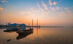 旭日将升,霞光满天,一湾清澈的海水把天空抱在怀里,渔船像一个睡熟的孩子,等候晨光将它叫醒。